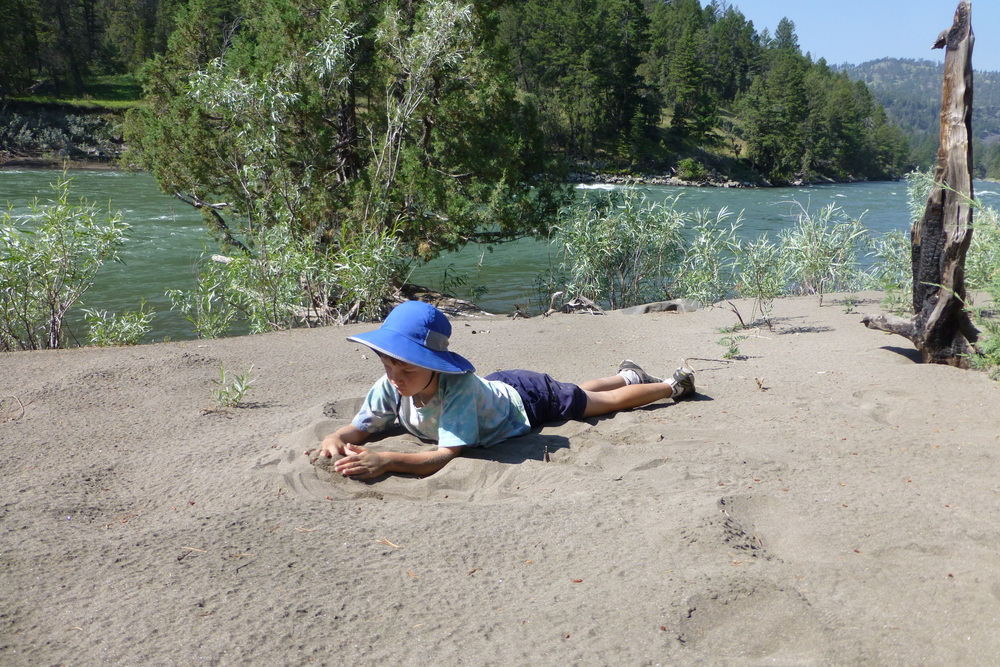 Boy playing in sand by river