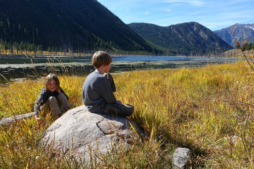 boys on rock by river in fall colors