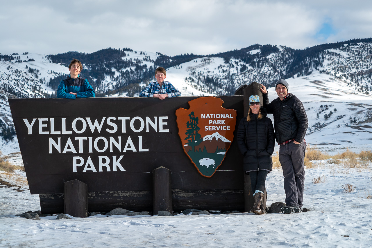 family standing in snow at Yellowstone National Park entrance sign in Gardiner, Montana