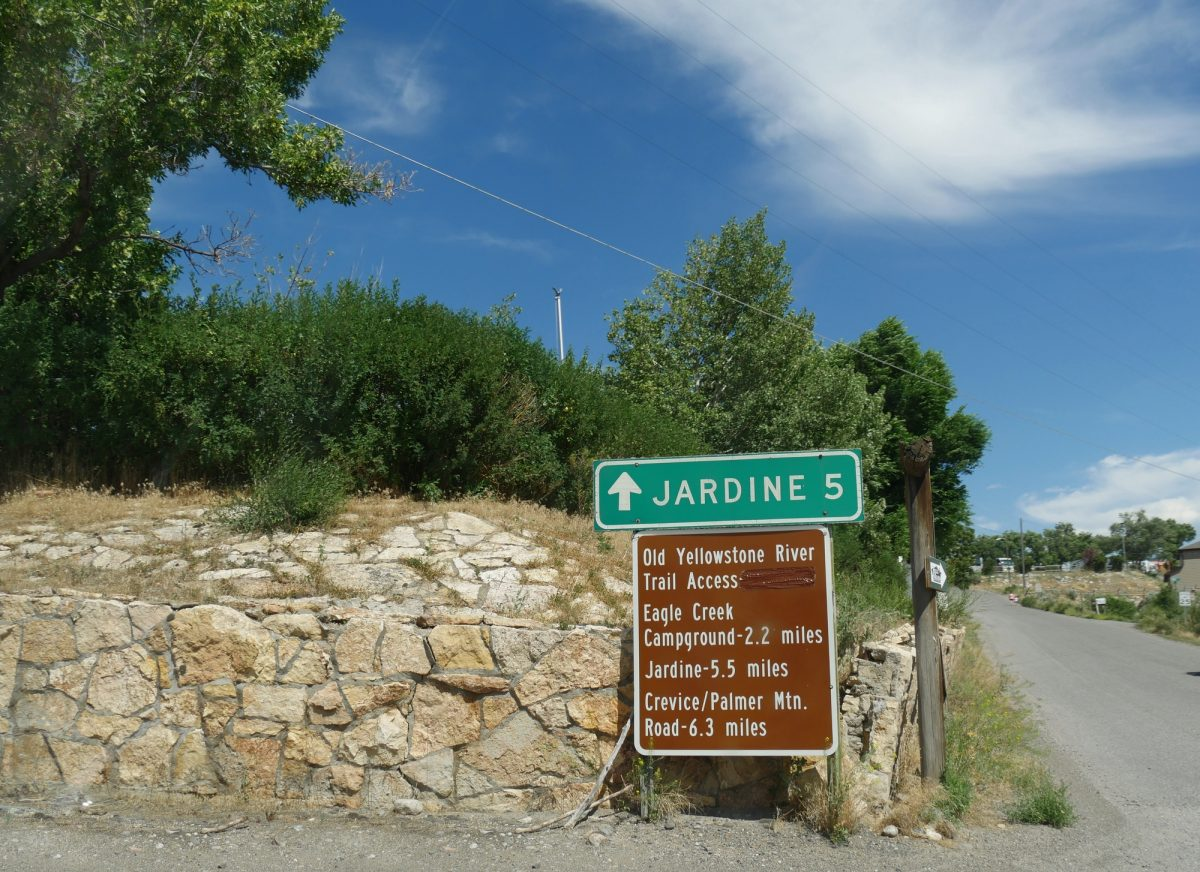 Roadside sign in Gardiner, Montana with directions to Jardine, Old Yellowstone River trail access and other destinations.