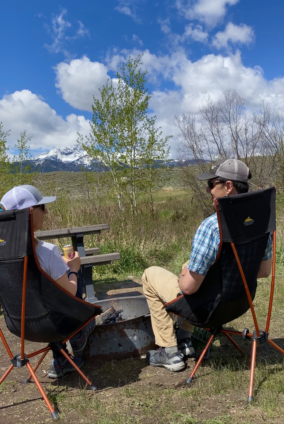 two people sitting in chairs around a campfire on a camping trip near Yellowstone